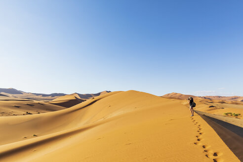 Africa, Namibia, Namib desert, Naukluft National Park, female tourist walking on dune - FOF10077