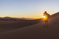 Africa, Namibia, Namib desert, Naukluft National Park, photographer on dune during sunrise - FOF10080