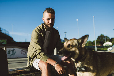 Portrait of content young man with his dog - RAEF02110