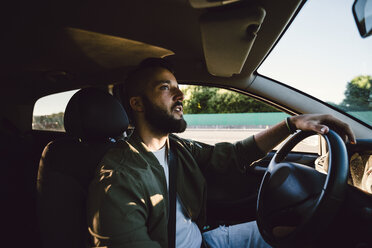Bearded young man looking at rear-view mirror while driving car - RAEF02113