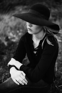 Young woman wearing black hat sitting on a meadow - JESF00093