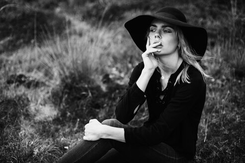 Portrait of pensive young woman wearing black hat sitting on a meadow - JESF00096