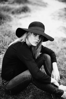 Portrait of young woman wearing black hat sitting on a meadow - JESF00099