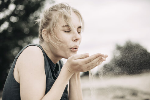 Portrait of young woman blowing sand in the air - JESF00102