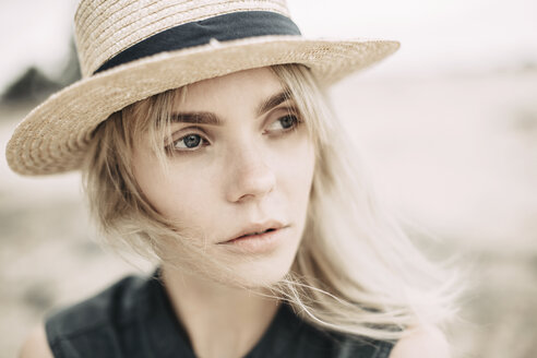 Portrait of daydreaming young woman wearing straw hat in nature - JESF00111