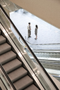 Mixed race pair of business people on the way to a meeting near a set of escalators. - MINF08936
