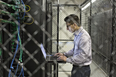 Hispanic man technician doing diagnostic tests on computer servers in a large server farm. - MINF08966