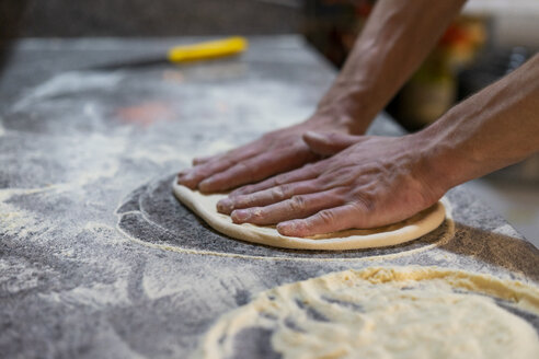 Close-up of pizza baker preparing pizza dough in kitchen - AFVF01437