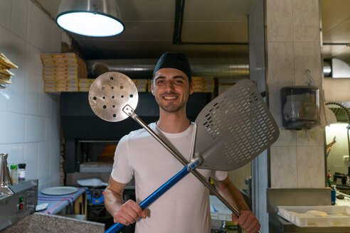Portrait of smiling pizza baker holding pizza peel and big skimmer in kitchen - AFVF01473
