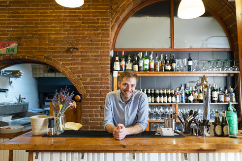 Portrait of smiling man leaning on counter of a pizzeria - AFVF01476