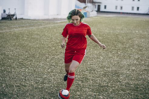 Young woman playing football on football ground running with the ball - VPIF00509