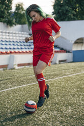 Young woman playing football on football ground dribbling with the ball - VPIF00515