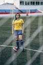 Young woman standing on football ground with the ball - VPIF00518
