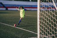 Young woman playing football on football ground shooting the ball - VPIF00521