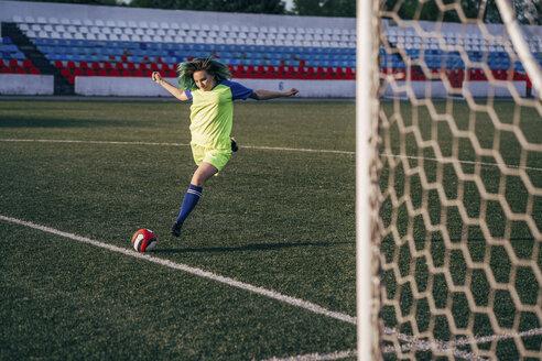Young woman playing football on football ground shooting the ball - VPIF00521