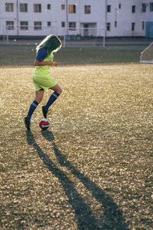 Young woman playing football on football ground dribbling with the ball - VPIF00524