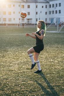 Young woman playing football on football ground balancing the ball - VPIF00527
