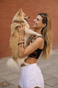 Smiling young woman holding her dog - ACPF00244
