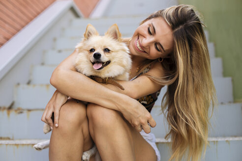 Smiling young woman sitting on stairs holding her dog - ACPF00247