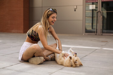 Pretty young woman smiling and caressing a dog - ACPF00253