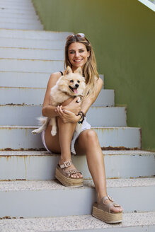 Smiling young woman sitting on stairs holding her dog - ACPF00256