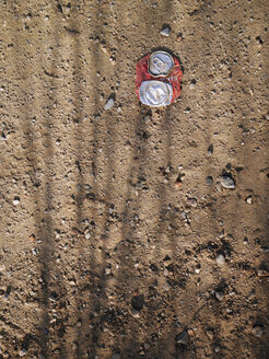 Crushed tin can on ground - JMF00418
