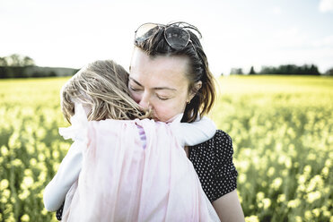 Little girl on her mother's arms in rape field - PSIF00010