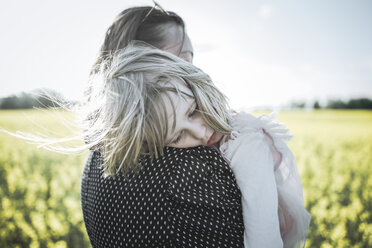 Portrait of little girl on her mother's arms in rape field - PSIF00025