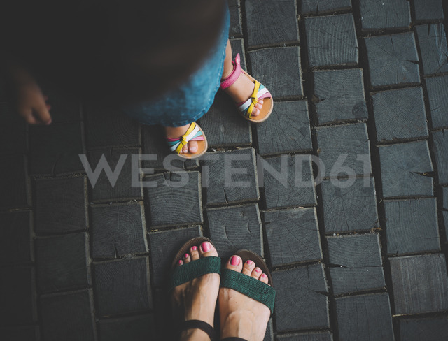 Feet of baby girl and her mother standing on wooden pavement, top view - GEMF02305