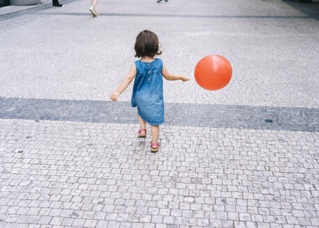 Back view of baby girl with red balloon walking on pavement - GEMF02308
