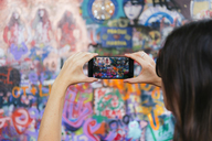 Czechia, Prague, woman taking photos of The Lennon Wall with smartphone - GEM02317
