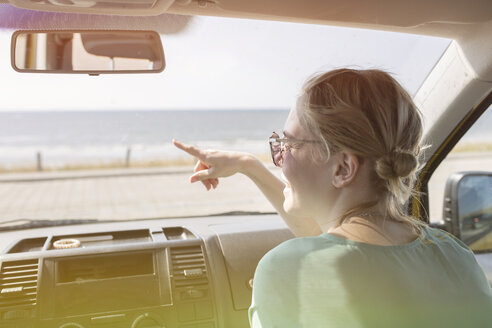 Happy young woman in a car pointing her finger - JESF00113
