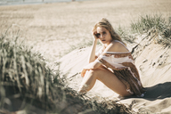 Portrait of a young woman sitting in beach dune - JESF00122