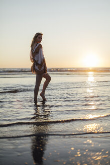 Portrait of a young woman standing in the sea at sunset - JESF00134