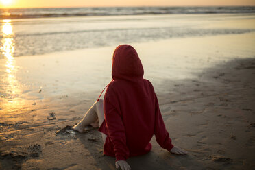 Young woman wearing red hooded jacket sitting on the beach at sunset - JESF00137