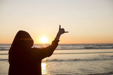 Young woman wearing red hooded jacket on the beach at sunset making hang loose gesture - JESF00140