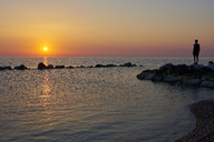Italy, Abruzzo, San Vito Chietino, Trabocchi coast, man looking at distance during sunrise - LOMF00740