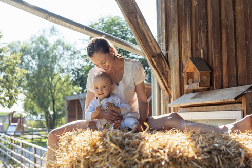 Happy mother and little daughter sitting in straw in a barn - DIGF04965
