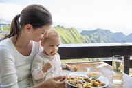 Germany, Bavaria, Oberstdorf, mother and little daughter having lunch at a mountain hut - DIGF04968