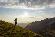 Germany, Bavaria, Oberstdorf, man on a hike in the mountains looking at view at sunset - DIGF04983