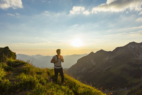 Germany, Bavaria, Oberstdorf, man on a hike in the mountains at sunset - DIGF04986