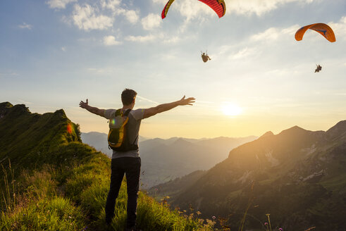 Germany, Bavaria, Oberstdorf, man on a hike in the mountains at sunset with paraglider in background - DIGF04989