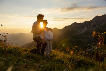 Germany, Bavaria, Oberstdorf, family with little daughter on a hike in the mountains at sunset - DIGF04992