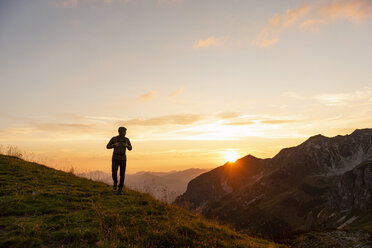 Germany, Bavaria, Oberstdorf, man on a hike in the mountains at sunset - DIGF04995
