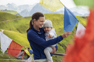 Germany, Bavaria, Oberstdorf, happy mother carrying little daughter on a mountain hut surrounded by pennants - DIGF05004