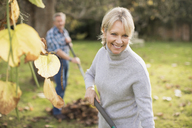 Portrait smiling, confident mature woman raking leaves in autumn backyard - HOXF03676