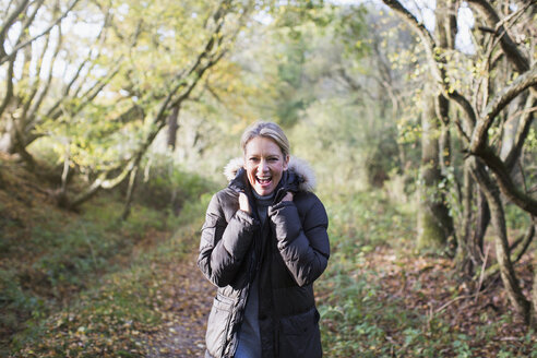 Portrait enthusiastic mature woman wearing parka in autumn woods - HOXF03682