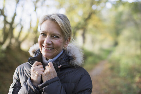 Portrait smiling, confident mature woman in parka in woods - HOXF03685
