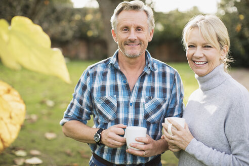 Portrait smiling, confident mature couple drinking coffee in autumn yard - HOXF03688