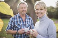 Portrait smiling, happy mature couple drinking coffee in backyard - HOXF03700